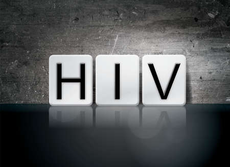The word HIV written in white tiles against a dark vintage grunge background. Stock Photo