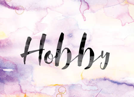 The word Hobby painted in black ink over a colorful watercolor washed background concept and theme. Imagens