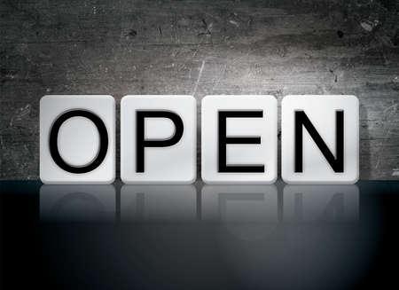 """Het woord """"Open"""" geschreven in witte tegels tegen een donkere vintage grunge achtergrond."""