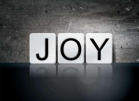 単語「喜び」暗いヴィンテージ グランジ背景に白いタイルで書かれました。