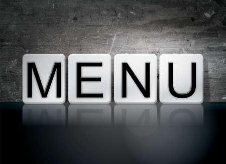 """Het woord """"Menu"""" geschreven in witte tegels tegen een donkere vintage grunge achtergrond."""