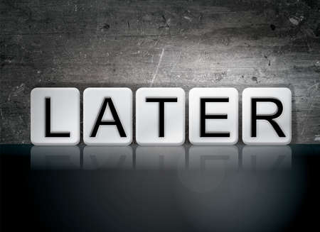 eventually: The word Later written in white tiles against a dark vintage grunge background. Stock Photo