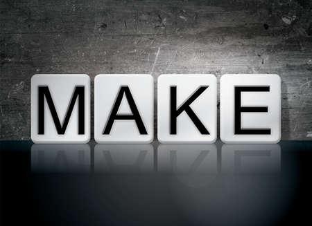 The word Make written in white tiles against a dark vintage grunge background. Stok Fotoğraf