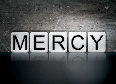 clemency: The word Mercy written in white tiles against a dark vintage grunge background.