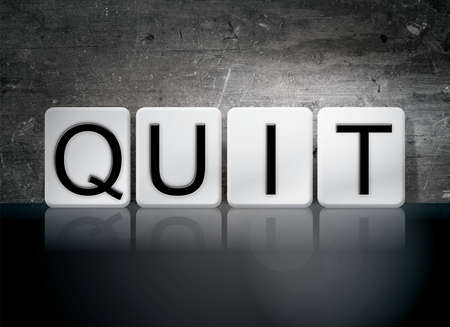 The word Quit written in white tiles against a dark vintage grunge background. Stock Photo