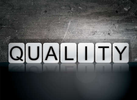 trait: The word Quality written in white tiles against a dark vintage grunge background. Stock Photo