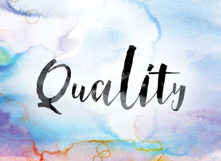 The word Quality painted in black ink over a colorful watercolor washed background concept and theme.