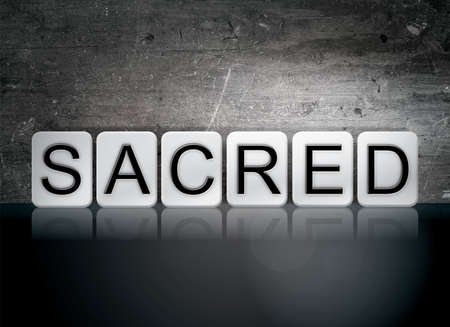 The word Sacred written in white tiles against a dark vintage grunge background.
