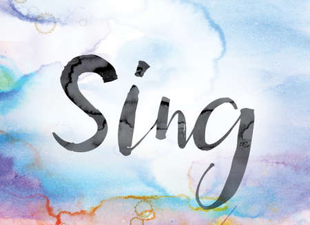 The word Sing painted in black ink over a colorful watercolor washed background concept and theme.