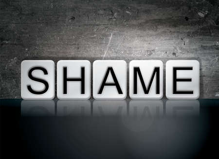 disgraceful: The word Shame written in white tiles against a dark vintage grunge background.