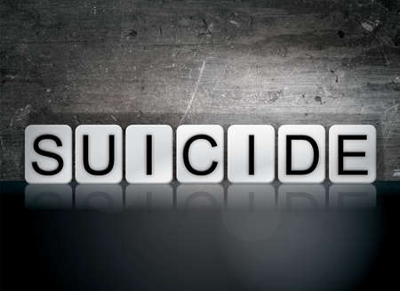 suicidal: The word Suicide written in white tiles against a dark vintage grunge background. Stock Photo