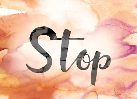 The word Stop painted in black ink over a colorful watercolor washed background concept and theme. Stock Photo