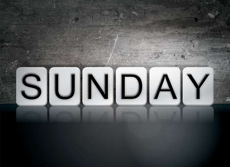 The word Sunday written in white tiles against a dark vintage grunge background. Stock Photo