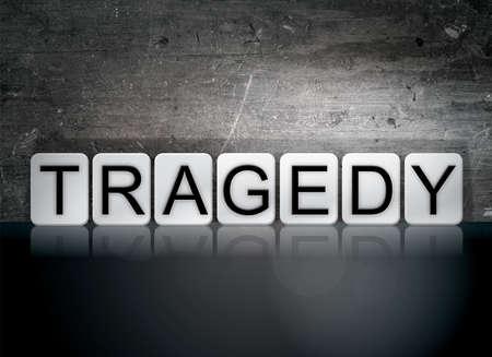 The word Tragedy written in white tiles against a dark vintage grunge background.