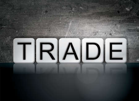 swapping: The word Trade written in white tiles against a dark vintage grunge background. Stock Photo