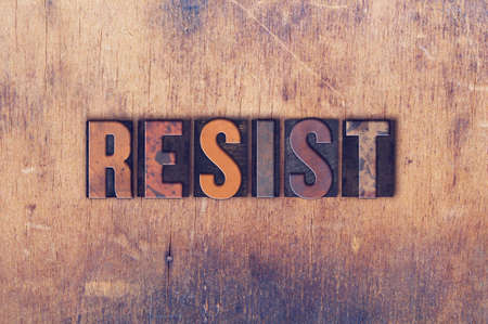 The word RESIST written in vintage wooden letterpress type.