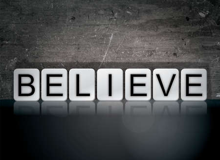 The word Believe concept and theme written in white tiles on a dark background.