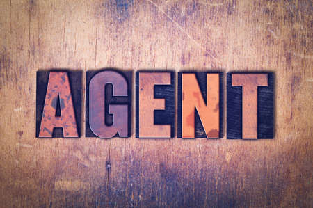 The word Agent concept and theme written in vintage wooden letterpress type on a grunge background.