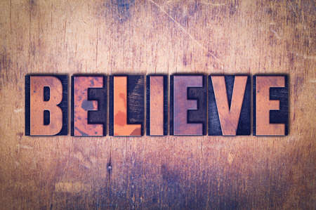 The word Believe concept and theme written in vintage wooden letterpress type on a grunge background.