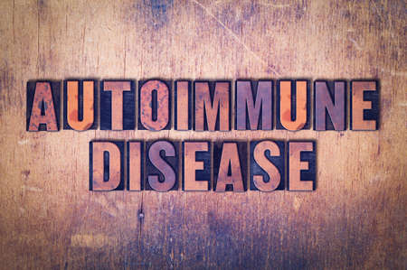 The words Autoimmune Disease concept and theme written in vintage wooden letterpress type on a grunge background.