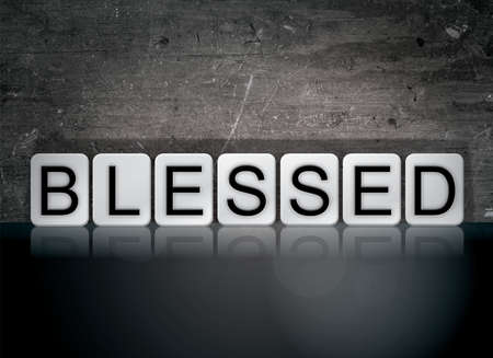 The word Blessed concept and theme written in white tiles on a dark background.