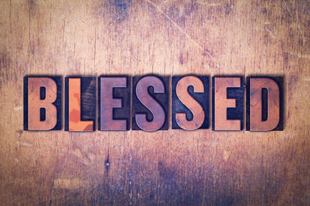 The word Blessed concept and theme written in vintage wooden letterpress type on a grunge background. Stock Photo