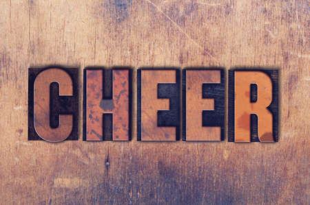 The word Cheer concept and theme written in vintage wooden letterpress type on a grunge background.