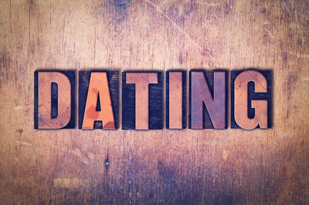 The word Dating concept and theme written in vintage wooden letterpress type on a grunge background.