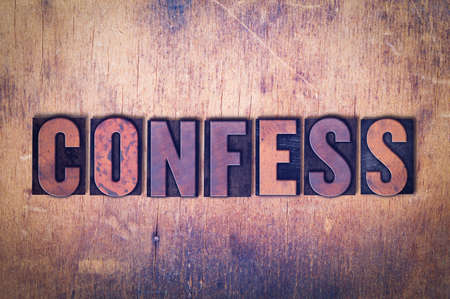 The word Confess concept and theme written in vintage wooden letterpress type on a grunge background. Stock Photo