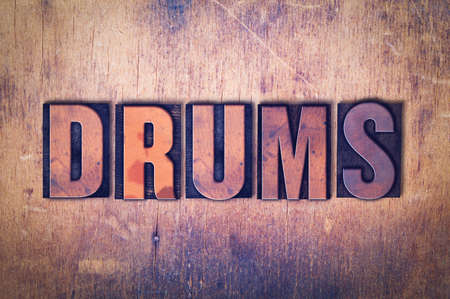 The word Drums concept and theme written in vintage wooden letterpress type on a grunge background.