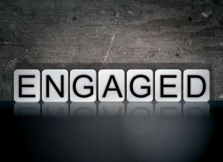 The word Engaged concept and theme written in white tiles on a dark background. Stock Photo