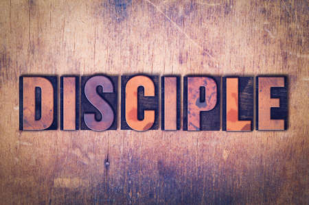 The word Disciple concept and theme written in vintage wooden letterpress type on a grunge background. Stock fotó