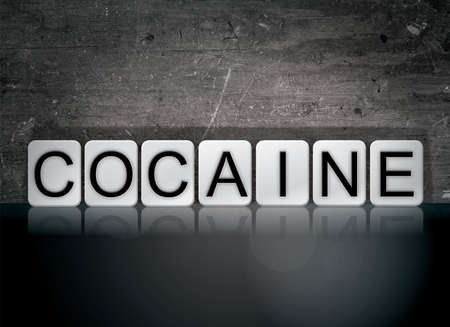 The word Cocaine concept and theme written in white tiles on a dark background. Stock Photo