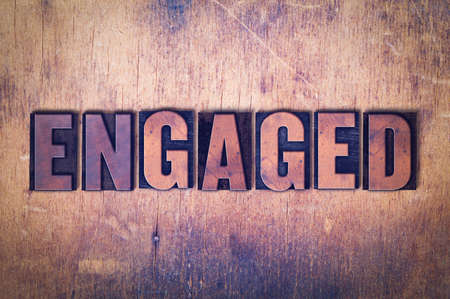 The word Engaged concept and theme written in vintage wooden letterpress type on a grunge background.