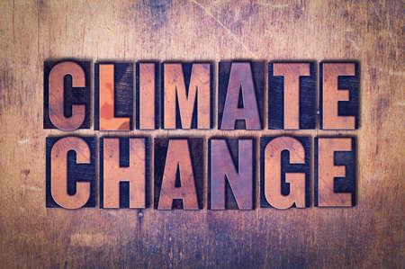 The word Climate Change concept and theme written in vintage wooden letterpress type on a grunge background.