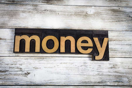 letterpress words: The word money written in wooden letterpress type on a white washed old wooden boards background.