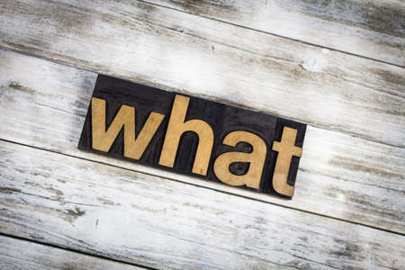 typescript: The word what written in wooden letterpress type on a white washed old wooden boards background. Stock Photo