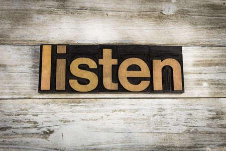 letterpress words: The word listen written in wooden letterpress type on a white washed old wooden boards background.