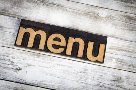 """Het woord """"menu"""" in houten letterzetseltype op een witte gewassen oude houten raadsachtergrond die wordt geschreven."""