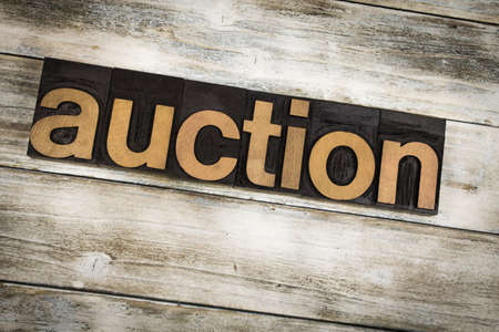 letterpress words: The word auction written in wooden letterpress type on a white washed old wooden boards background. Stock Photo