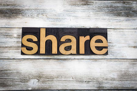 shared sharing: The word share written in wooden letterpress type on a white washed old wooden boards background.