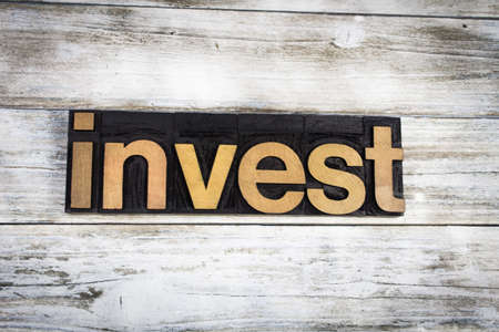 stockmarket: The word invest written in wooden letterpress type on a white washed old wooden boards background.