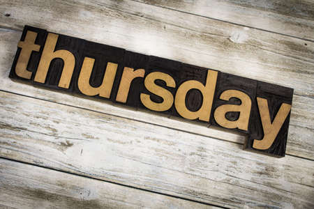 typescript: The word Thursday written in wooden letterpress type on a white washed old wooden boards background. Stock Photo