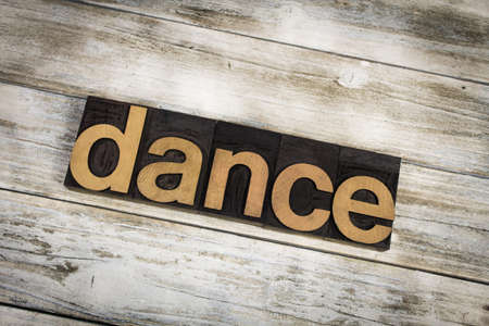 The word dance written in wooden letterpress type on a white washed old wooden boards background.