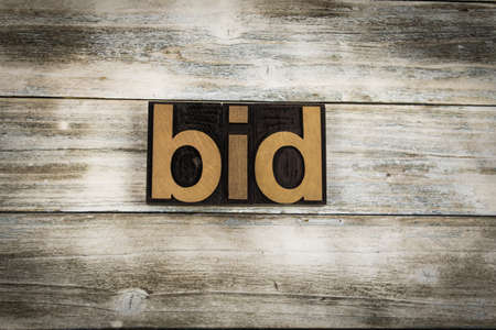 typescript: The word bid written in wooden letterpress type on a white washed old wooden boards background. Stock Photo