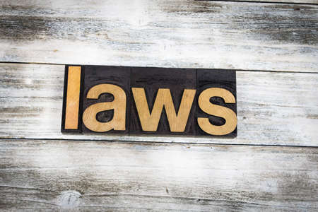 letterpress words: The word laws written in wooden letterpress type on a white washed old wooden boards background. Stock Photo