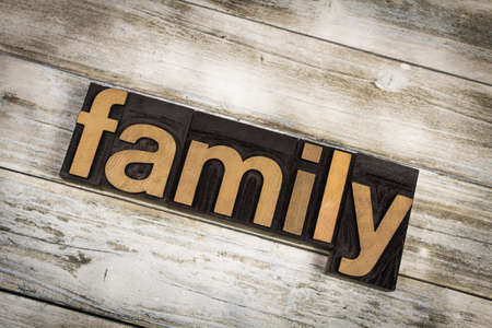 The word family written in wooden letterpress type on a white washed old wooden boards background.