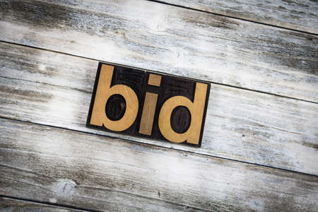 bidding: The word bid written in wooden letterpress type on a white washed old wooden boards background. Stock Photo