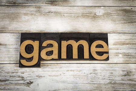 typescript: The word game written in wooden letterpress type on a white washed old wooden boards background. Stock Photo