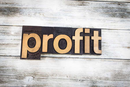The word profit written in wooden letterpress type on a white washed old wooden boards background.
